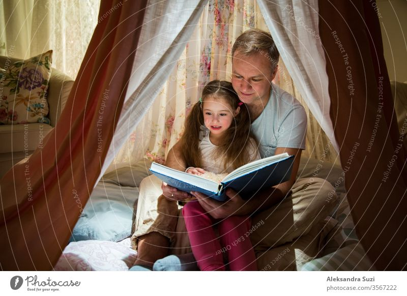 Family quality time. Father and daughter sit in homemade pink tent with flowers, read big book, look at each other, smile and laugh. Cozy stylish room. Family bonds concept