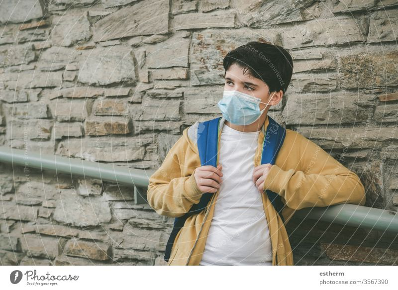 kid with medical mask and backpack waiting at the school door coronavirus Child Virus Epidemic covid-19 School schuler pandemic Quarantine back to school City