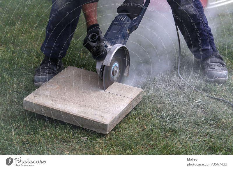 Industrial construction worker using a professional angle grinder brick cinder circular closeup collar concrete copper cordless craft cutter danger debris disc