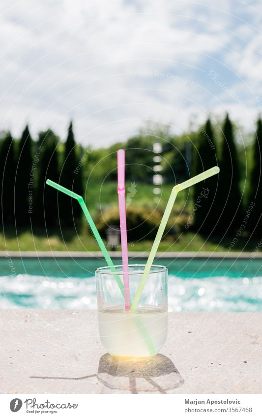 Glass of lemonade with three straws by the swimming pool alcoholic aqua beverage blue cocktail cold colorful colors cool copy drink enjoy exotic fresh freshness