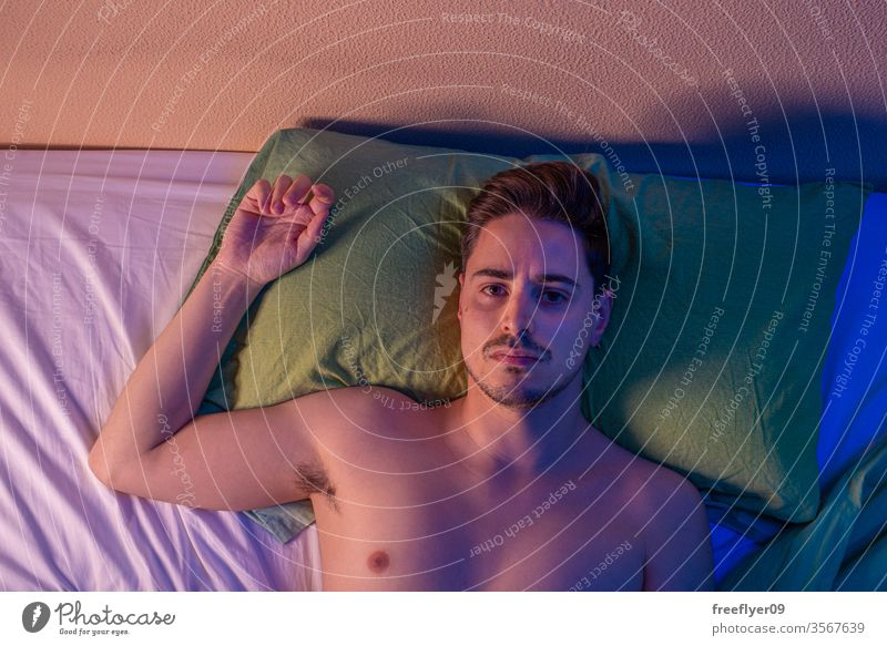 Portrait of a man on the bed from above at night portrait male quarantine depression pillow naked nude coronavirus covid-19 isolation self-isolated insomnia