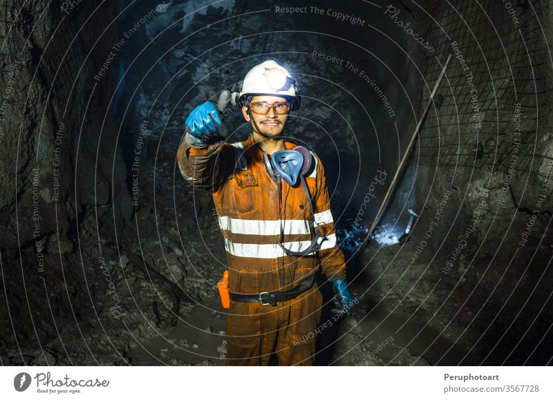 Miner in the mine. Well-uniformed miner inside mine raising thumb cave industrial underground shaft one outdoor outfit overalls person positive power production