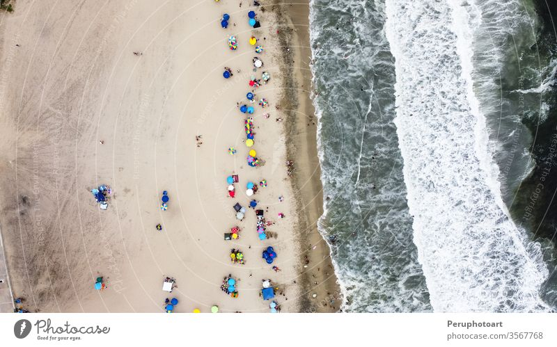 Beautiful aerial view with drone to one of the beaches south of Lima in Peru where you can see umbrellas and people enjoying the summer. sand sea nature