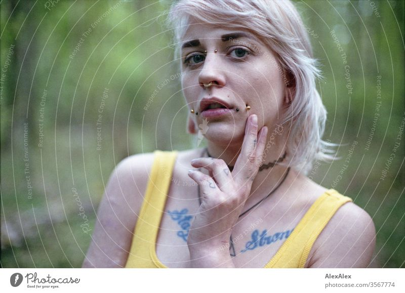 Analogue portrait of a young woman with piercings, tattoos and tunnel Woman girl Blonde Piercing Jewellery Assecoires Shoulder shirt Shirt already out look