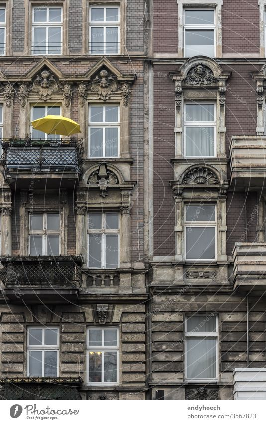 Yellow parasol on a balcony of an old building ancient apartment apartments architectural architecture balconies Berlin brick city cityscape color colorful
