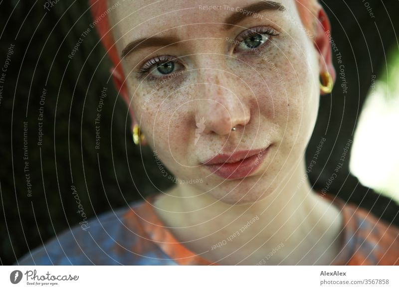 Portrait of a young woman in front of a tree Woman 18-25 years already Slim Freckles Red-haired Jewellery Piercing tattooing Face Fair-skinned Short-haired