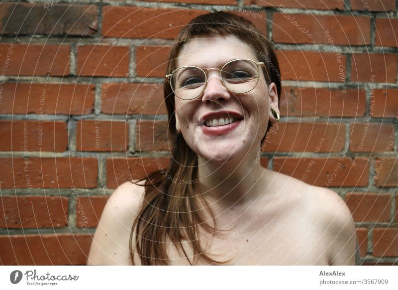 Portrait of a laughing young woman in front of a brick wall Woman Youth (Young adults) already Strong Alternative great Piercing Skin Intensive Looking look