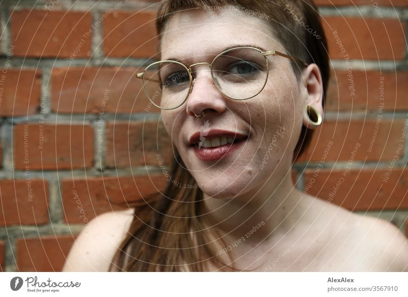 Portrait of a young woman in front of a brick wall Woman Youth (Young adults) already Strong Alternative great Piercing Skin Intensive Looking look watch Stand