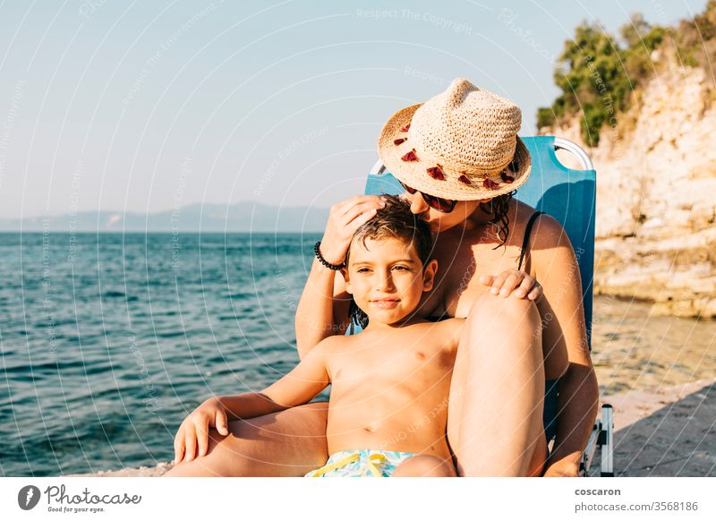 Mother and son relaxing on the coast near the sea beach boy caucasian child childhood coastline day enjoying enjoyment exotic family fun hammock happiness happy