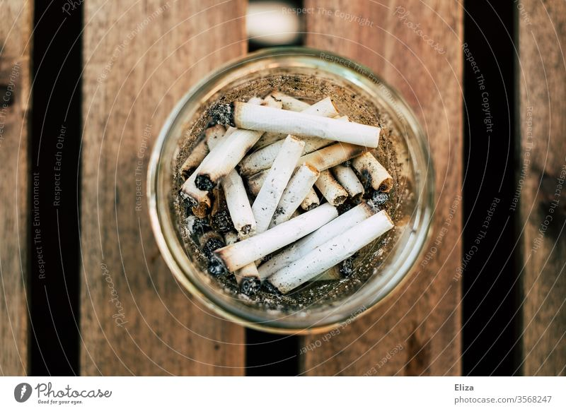 A round glass as ashtray with many cigarette butts in it from bird's eye view Ashtray dumb cigarettes Cigarette Butt Smoking homemade Roll-up cigarette Nicotine