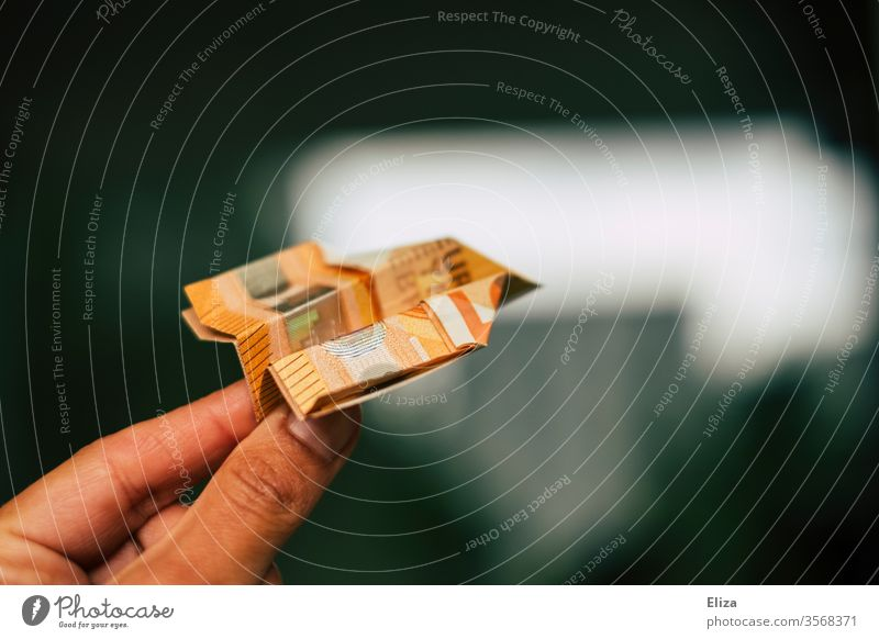 A hand flies a paper airplane folded from a banknote. Investment, investment. Paper plane Money Bank note Flying travel vacation Costs vacation budget Expensive