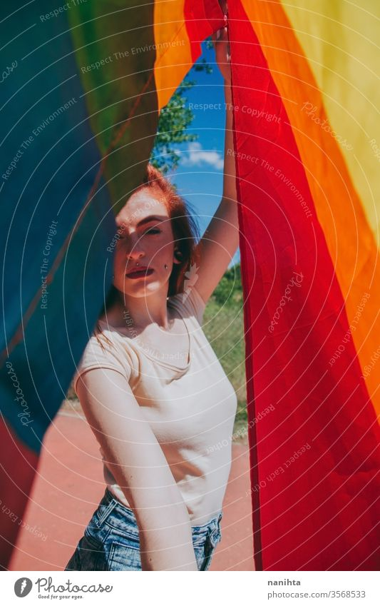 Young woman covering by a rainbow flag lgbti gay pride party rain bow homosexual lesbian color colorful outdoor social issue gender equality society free