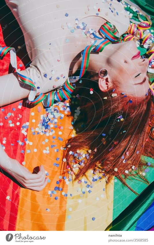 Young redhead woman celebrating gay pride day lgbti party flag rain bow homosexual lesbian color colorful outdoor social issue gender equality society free