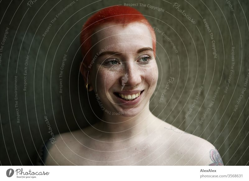 Portrait of a laughing young woman in front of a concrete wall Woman 18-25 years already Slim Freckles Concrete Wall (building) Red-haired Jewellery Piercing