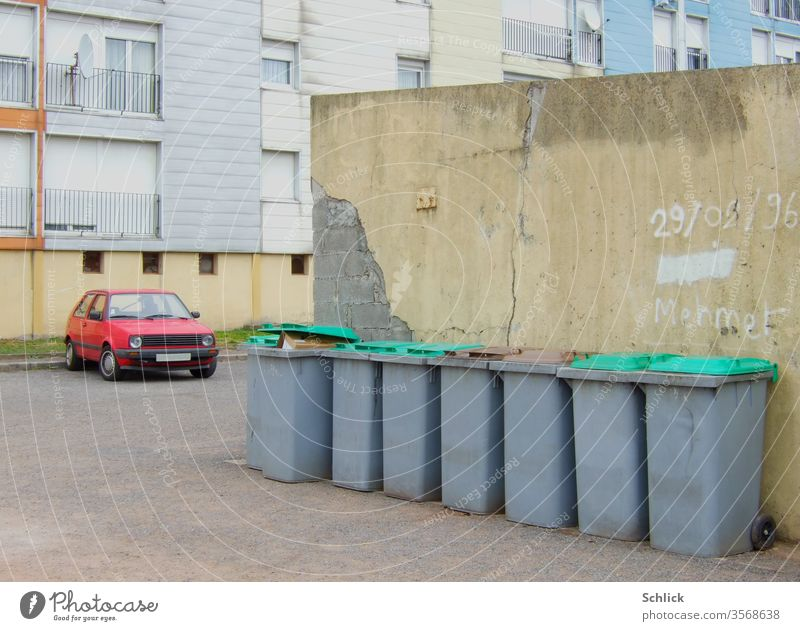 Old apartment block with red car and a row of garbage cans with green lids block of flats Red Waste bins Row Wall (barrier) Date Mehmet Text dilapidated Gloomy