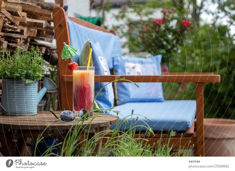 Kiba with drinking straw, strawberry and umbrella, sunglasses, as well as a garden bench with blue cushions are ready for a short break Cherry Banana Juice