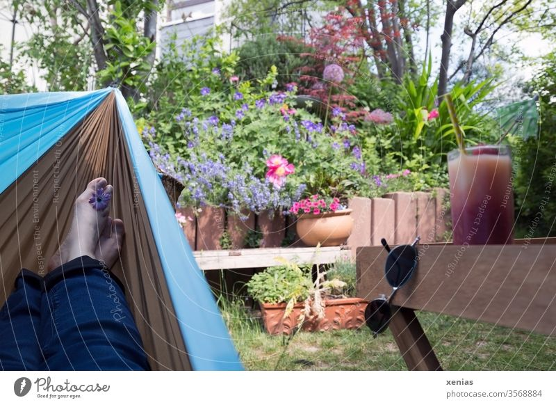 Feet in a hammock overlooking the garden and drink provided - deep relaxation guaranteed Hammock foot Garden Relaxation Sunglasses Beverage Juice Glass bleed