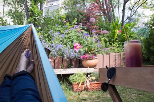 Feet in a hammock overlooking the garden and drink provided - deep relaxation guaranteed Hammock feet Garden Relaxation Sunglasses Beverage Juice Glass Blossom