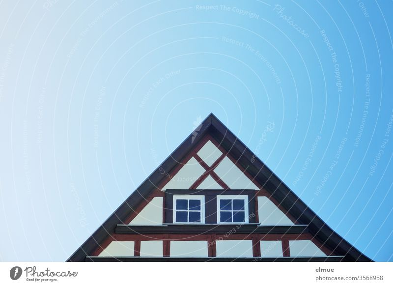 Gable of a renovated half-timbered house with two windows and blue colour gradient in the sky Half-timbered house Triangle pediment Window Blue Color gradient