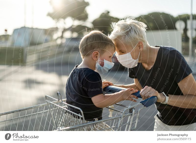 Mother joyfully playing with kid sitting in shopping cart. Both wearing protective face mask. woman mother baby child consumer corona coronavirus happy young