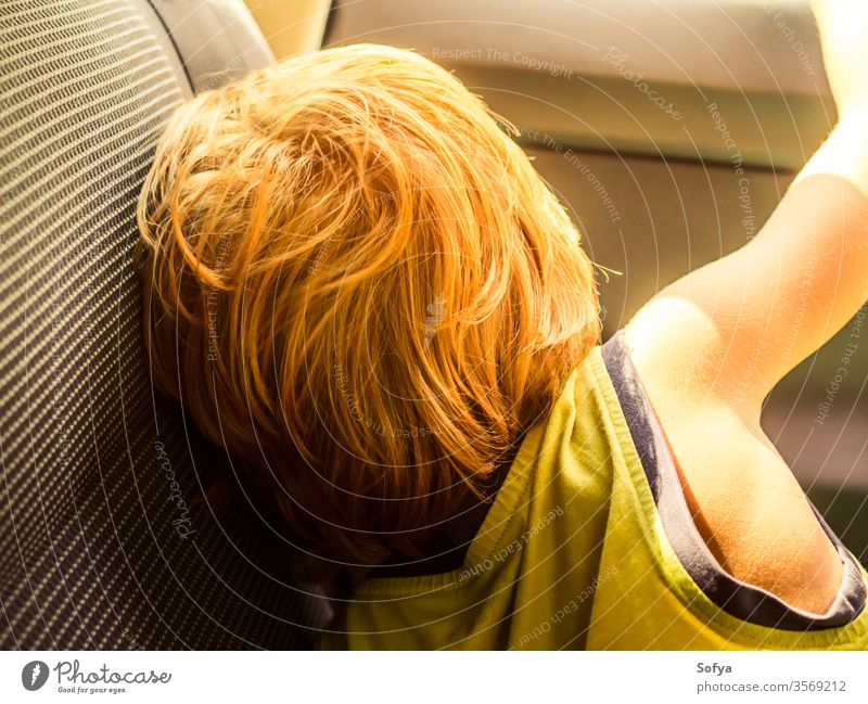 Little boy travelling in a car in summer little child enjoy sun sunny day light t-shirt yellow blonde caucasian kid vacation holiday natural young back tired