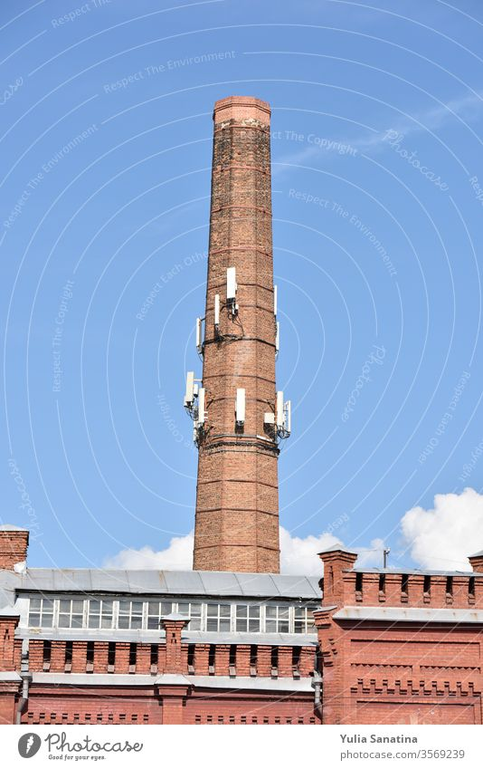 old chimney with modern antennas on it futuristic time machine brick red pipe old factory 4G 5G technology city progress