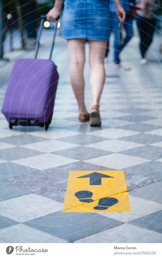 tourist with suitcase walking on a city street marked with social distance safety signs traveller covid-19 label holiday pandemic coronavirus woman