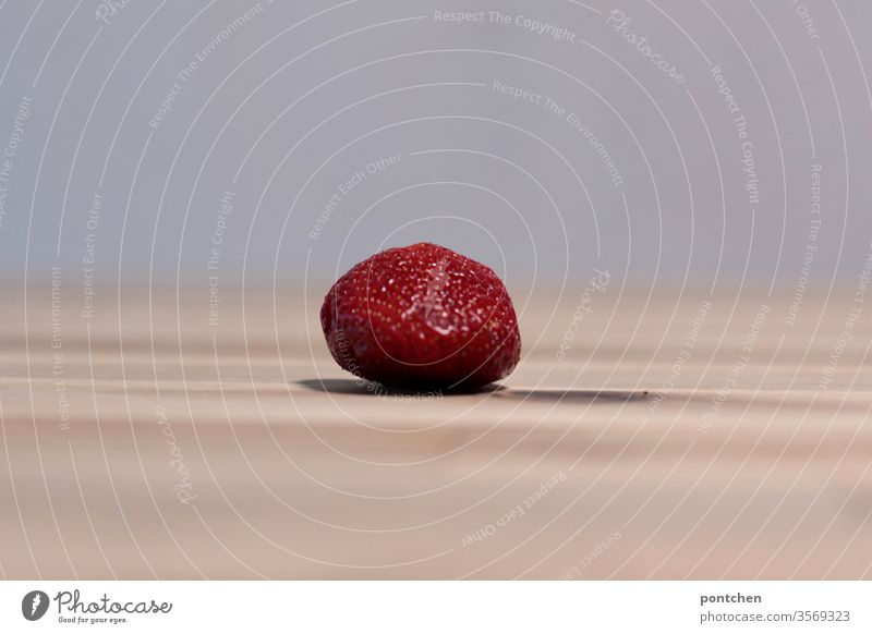 A single strawberry lies on a wooden table and casts a shadow Shadow Healthy Eating fruit vitamins Red Individual Table Nutrition Food Organic produce Delicious