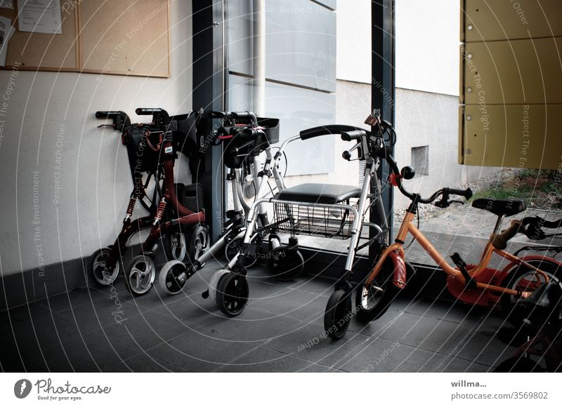 Rollator and children's bicycle at the entrance Kiddy bike Walkers Walking aid walker turned off antechamber Entrance Parked Assisted living togetherness