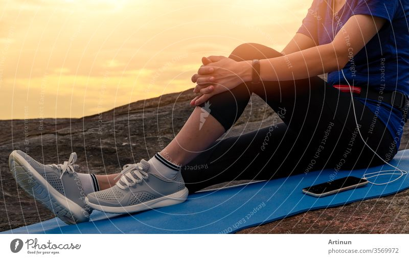 Woman sit and relax on yoga mat and listen to music via smartphone at stone beach by the sea . Woman outdoor workout. Fit girl wear smart band. Healthy, chill out lifestyle. Relax on summer vacations.