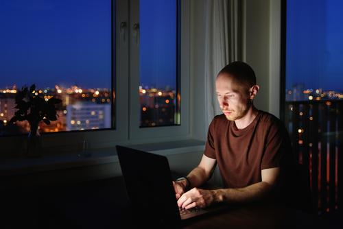 Man working on laptop from home at night business computer internet notebook insomnia addiction wireless communication dark sitting using desk man technology