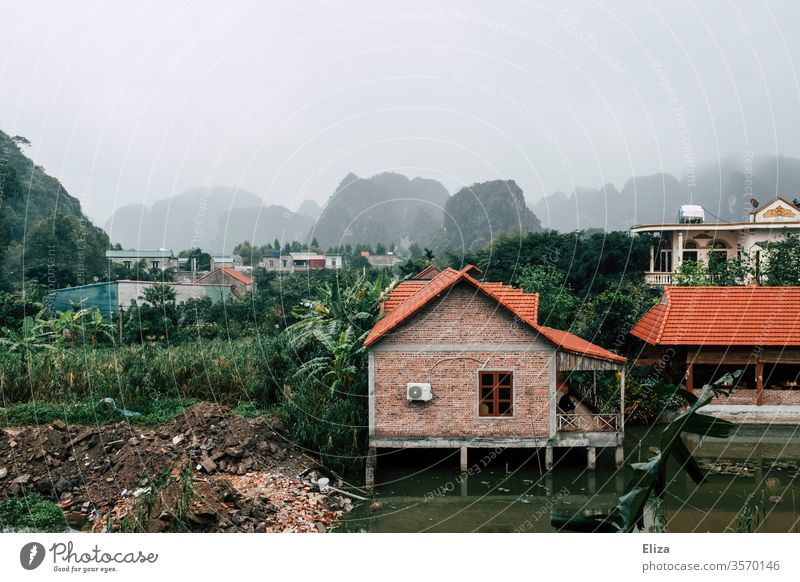 Landscape with houses in Vietnam foggy Ninh Binh Water stilts Green South East Asia Limestone rocks roofs Village