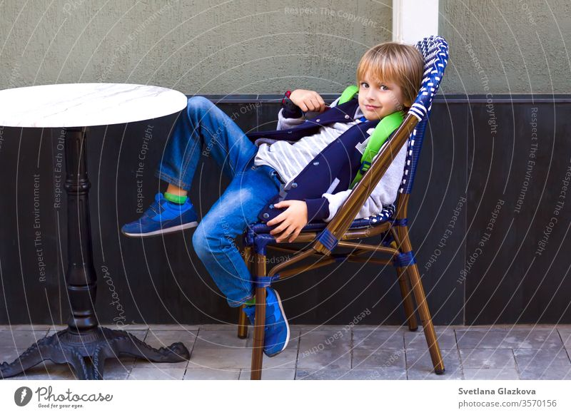 The boy sits on a chair in a city cafe. young in cafe sitting at cafe people coffee table hipsters restaurant family eating food restaurant child cute street