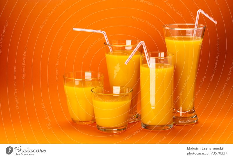 Glasses of orange juice isolated on colour orange background glass copy space fresh straw cocktail healthy food concept close up white fruit drink squeezed
