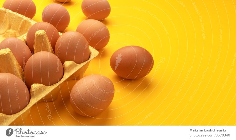 Brown chicken eggs in cardboard box on yellow background brown banner fresh farm copy space text organic food easter ingredient nature protein breakfast raw