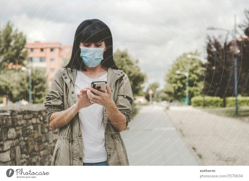 woman wearing medical mask With his smartphone on the street coronavirus young woman epidemic pandemic quarantine covid-19 app mobile technology portrait