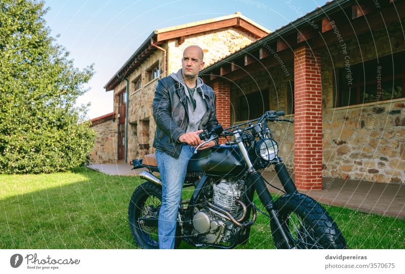 Man riding custom motorbike young man biker cafe racer posing vintage retro rider vehicle shaven head motorcycle transport fashion adult attractive one people