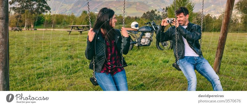 Young man taking a picture of his girlfriend on the swings couple taking picture camera happy motorcycle leather jacket biker banner web panoramic panorama