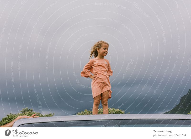 Child stands on the roof of a car and the wind blows her hair back Hawaii Gale Beach Sky Coast Clouds Colour photo Nature Wind Exterior shot Landscape Storm