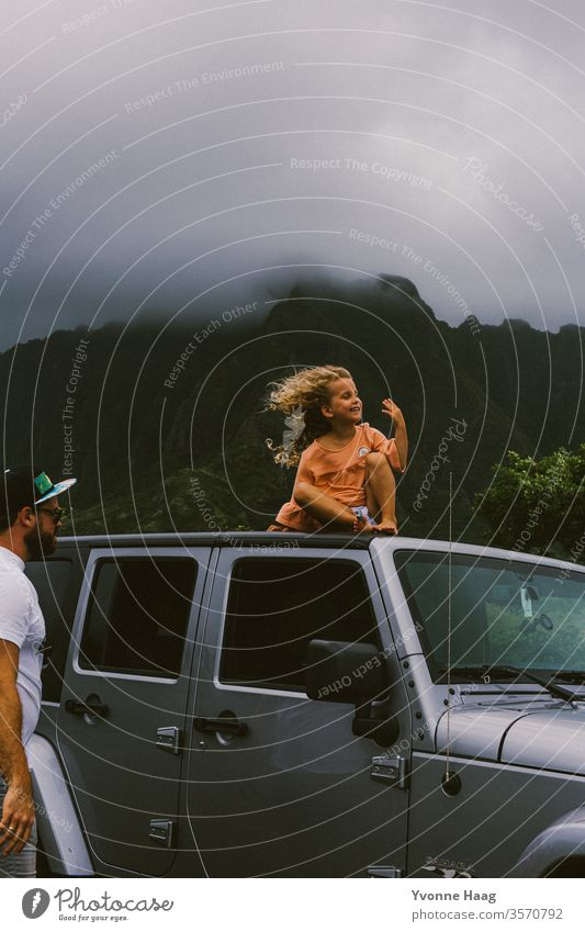 Child sits on the roof of a car and the wind blows her hair back Hawaii Gale Beach Sky Coast Clouds Colour photo Nature Wind Exterior shot Landscape Storm Water
