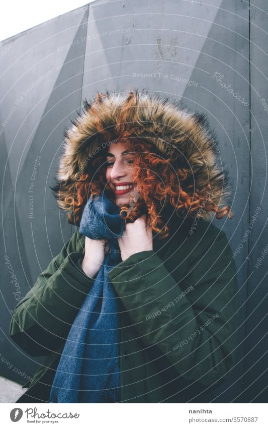 Beautiful portrait of an attractive redhead woman wearing winter clothes pretty face youth lifestyle curly hair ginger scarf warm model fashion trendy freckles