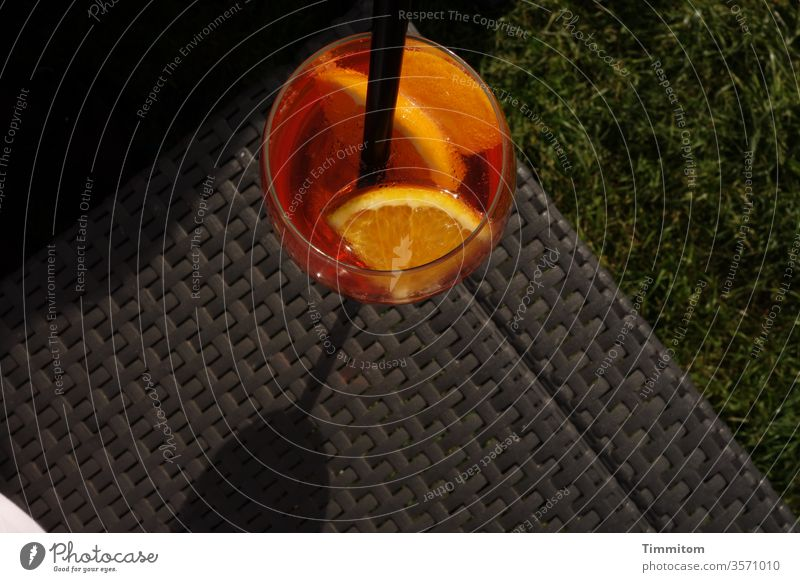 The drink waits in the evening sun Glass straw Alcoholic drinks celebration Drinking Orange slice Beverage Cocktail Light Evening Black conceit