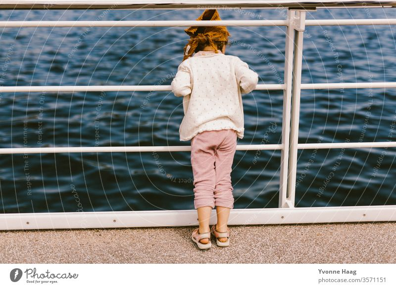 Child looks through the parapet into the sea Sand Beach Ocean Water Waves Surf Coast Sky Blue Clouds Horizon Nature Far-off places Landscape White