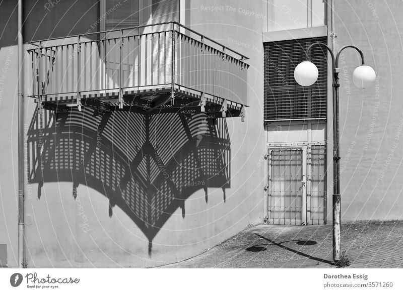 Balcony and street lamp throw shade Shadow Part of a building House (Residential Structure) Wall (barrier) Black and white photo Exterior shot Deserted Sun Day