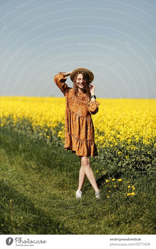 stylish young woman in straw hat in a field of yellow flowers. Girl in a floral dress. background with yellow flowers and blue sky girl portrait fashion spring