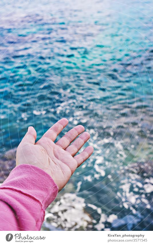 Female hand with an open palm reaches for surface of the water world oceans day hope man woman sea blue concept pov touch safe protect restore protection
