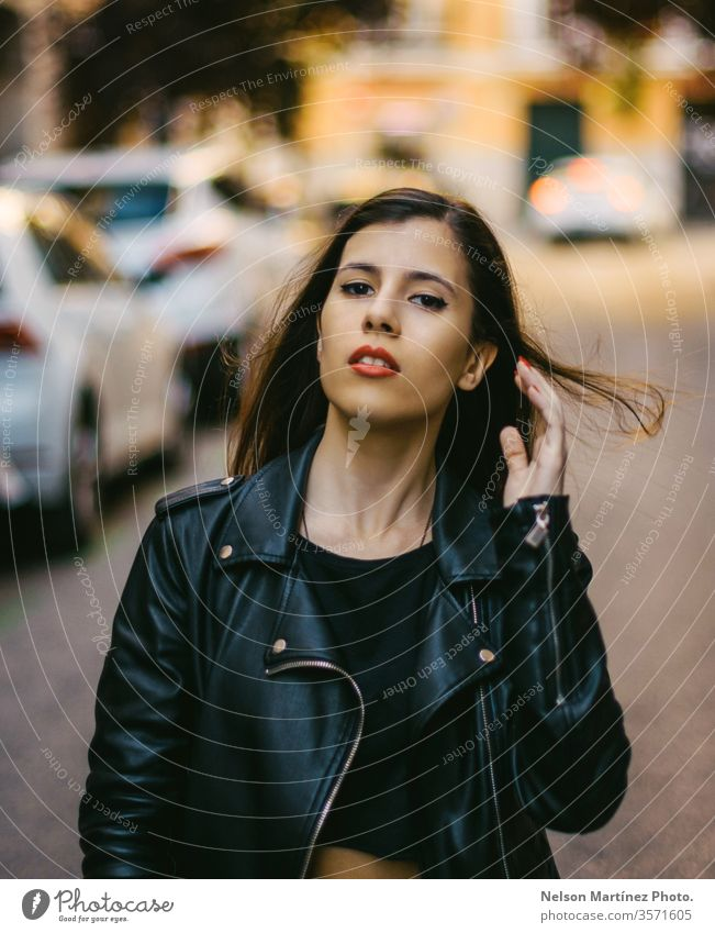 Portrait of a cute model wearing denim jacket. bokeh lights brunette face trendy natural real people Exterior shot Loneliness Dress Young woman Woman