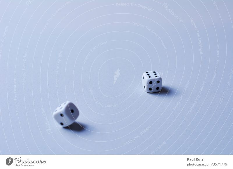Two dice in motion, on white background, cube desk rolling die winning winner tossing chance betting loss wood luck addiction entertainment casino choice wooden