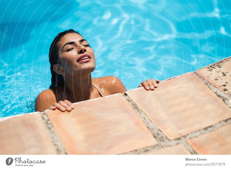 Mixed race young woman relaxing in water at swimming pool mixed race beautiful attractive bikini tanned skin girl sunbathing vacation model lifestyle resort