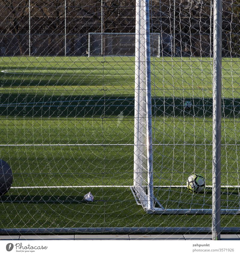 View along the football field from goal to goal. The front goal is cut, a ball is behind the line, wide lateral shadow casts on the field Football pitch